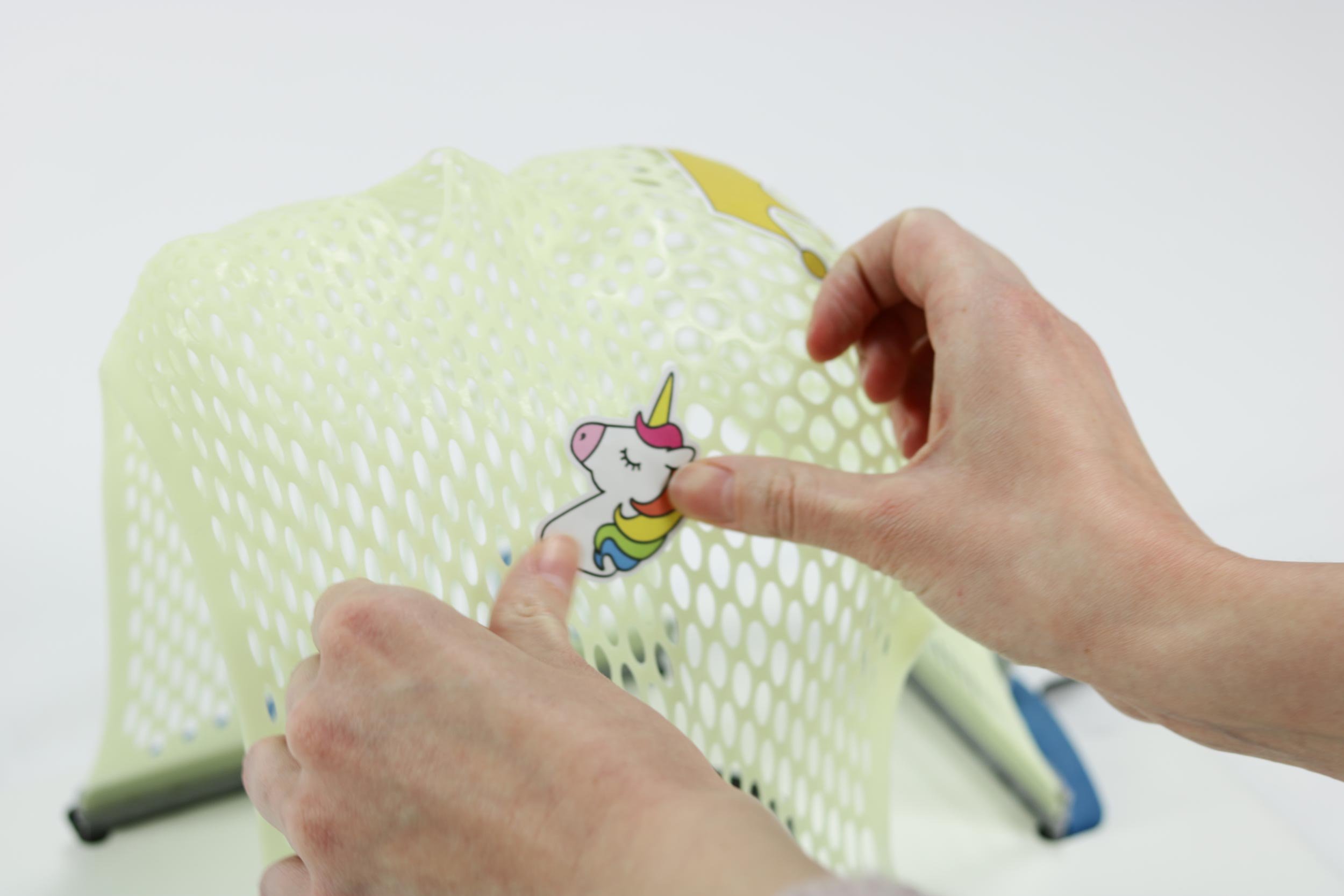 Sticking a unicorn sticker on a thermoplastic mask